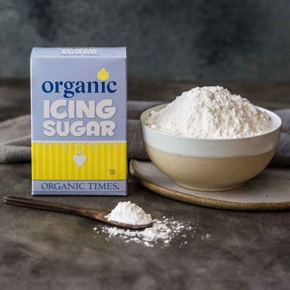 Organic Times Icing Sugar packaging next to a bowl of icing sugar and spoon.