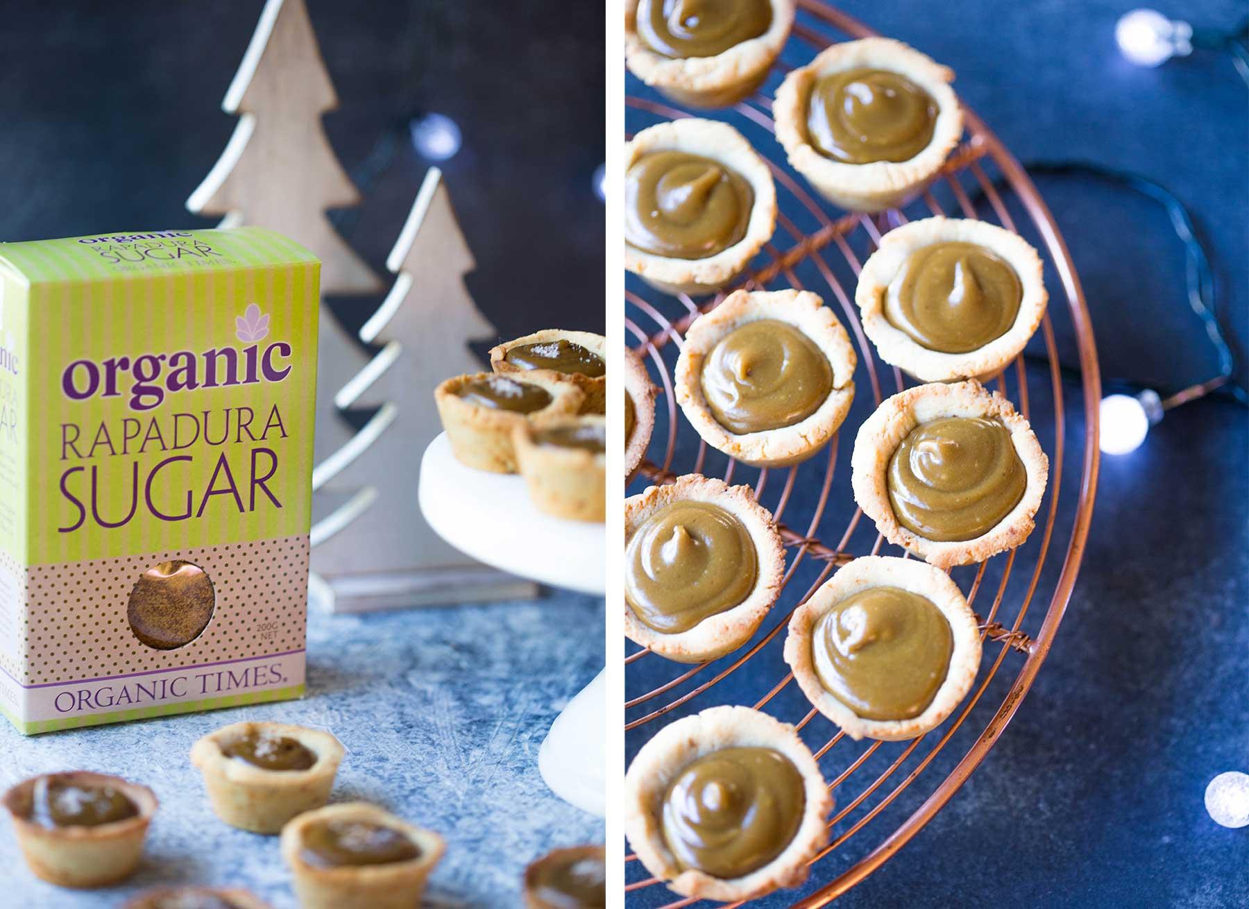 Salted caramel tarts on a cake stand next to Organic Times Rapadura Sugar box and Christmas decorations