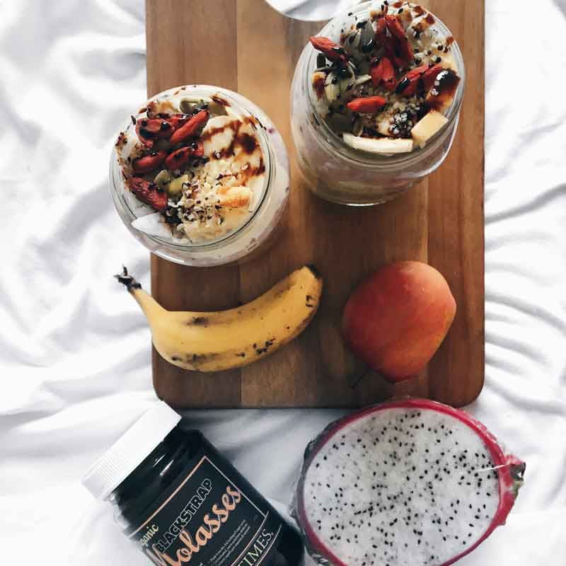 A jar of Organic Times Molasses next to jars of fruit and yoghurt parfait