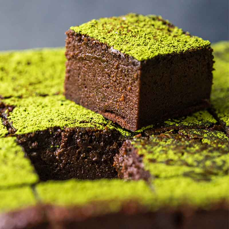 A piece of chocolate brownie with matcha on top